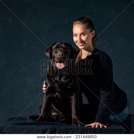 The Young Woman Hugging Black Labrador Dog Taken Against Black Backdrop At Studio