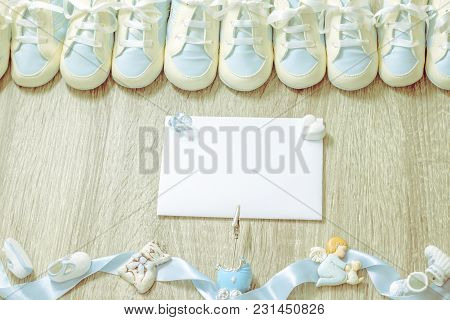 Baby Blue Bootees With Small Cute Accessories And White Paper On Wooden Background For Boy Newborn B