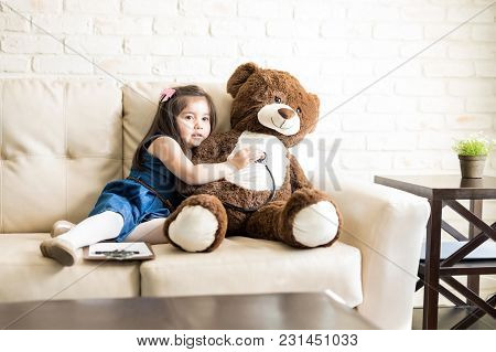 Beautiful Girl Playing Little Doctor Examine Teddy Bear With Stethoscope In Living Room