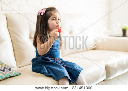 Beautiful Little Baby Girl Sitting On Sofa And Blowing A Soap Bubbles In The Living Room