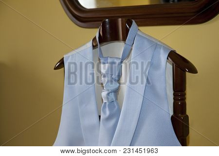 Light Blue Vest And Tie Hanging On A Wooden Hanger