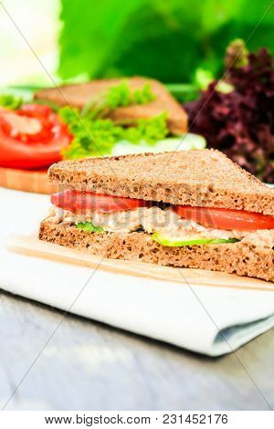 Sandwich With Rye Brown Bread, Ripe Tomatoes, Cucumbers And Tuna Fish For Healthy Snack On A Napkin