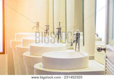 Row Of White Ceramic Wash Sink Basins And Faucet With Mirror In The Restroom