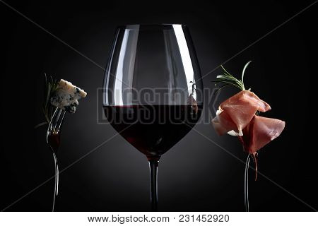 Glass Of Red Wine With Blue Cheese And Prosciutto On A Black Background.