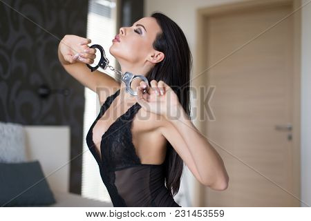 Sexy Woman In Underwear Holding Handcuffs In Bedroom, Indoors