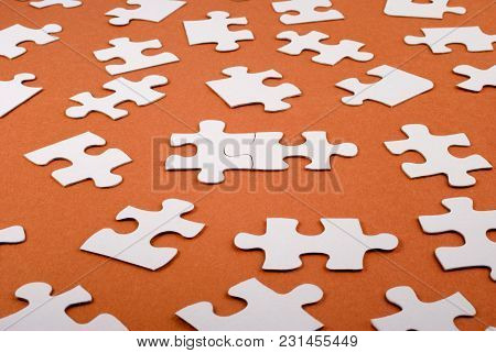 Lots Of Jigsaw Pieces Spread Out, With Two Joined Together. This Is A Simple Cardboard Jigsaw On A R