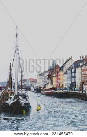 Copenhagen's Famous Nyhavn Harbour With The Typical Colorful Houses And Restaurants Along The Iced C