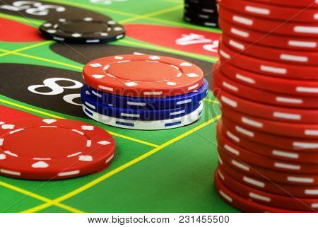 A roulette table and chips, bets are being placed. Concepts of gambling, luck, taking a chance. Focus on centre chips. poster