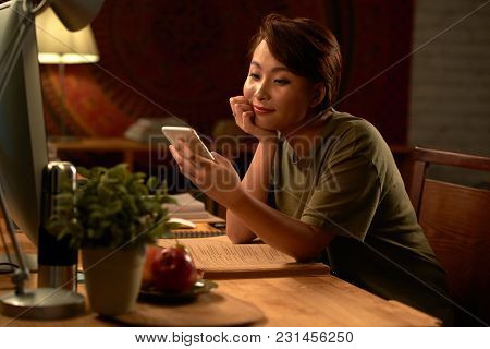 Pretty Vietnamese Young Woman Smiling When Reading Text Message On Her Phone
