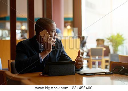 African-american Businessman Sitting In Cafe And Talking On The Phone