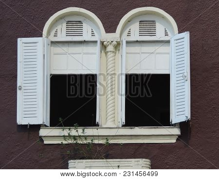 Two Windows Open On The Facade Of An Old Brown House