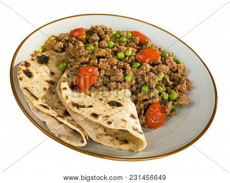 A Plate Of Beef Or Lamb Curry With Peas And Cherry Tomatoes And Chapatis, Isolated On White, And Wit