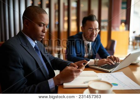 Unsmiling Businessman Checking Smartphone At Meeting In Cafe