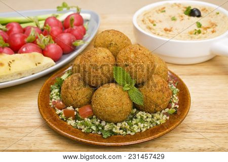 Middle Eastern Treats, Falafel Sitting On A Bed Of Tabbouleh, With Hummus And Radishes.