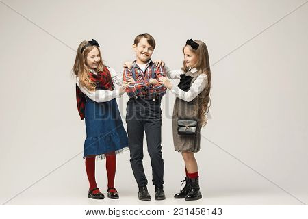 Cute Stylish Children On White Studio Background. Two Beautiful Teen Girls And Boy Standing Together