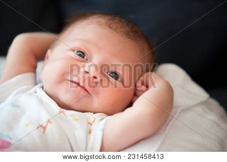 Newborn baby infant looks puzzled with her eyes open and har forehead wrinkled