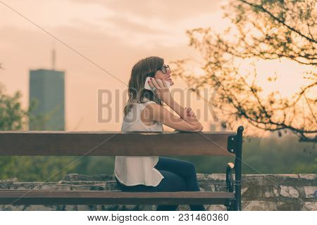 Smiley Girl Sitting On A Bench And Talking On The Phone.