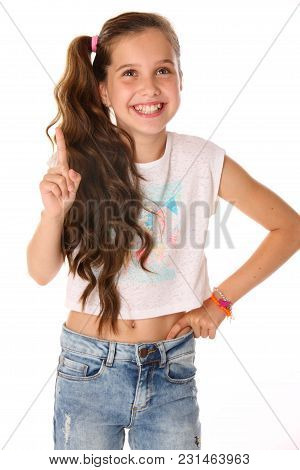 Portrait Of Happy Slender Cheerful Teenage Girl. The Child Elegantly Poses Makes Funny Faces And Smi