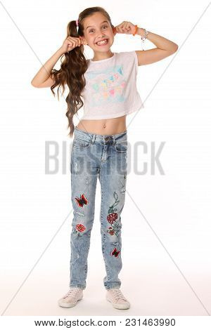 Portrait Of Happy Slender Cheerful Teenage Girl In Full Body. The Child Elegantly Poses Makes Funny