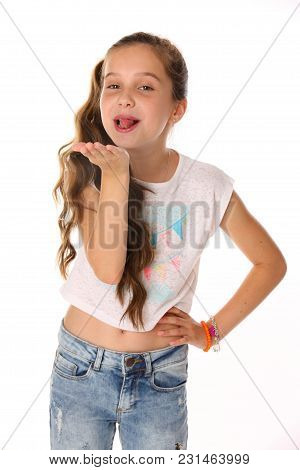 Portrait Of Happy Slender Cheerful Teenage Girl. The Child Elegantly Poses Makes Funny Faces And Sho