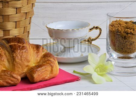 An Vintage Empty Coffee Cup On A Saucer, Fresh Croissant On The Rose Table-napkin , Item Of Brown Ba