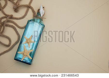 Nautical Theme Backdrop, Decorative Bottle With Shells, Starfish On Neutral Ivory Background. Place