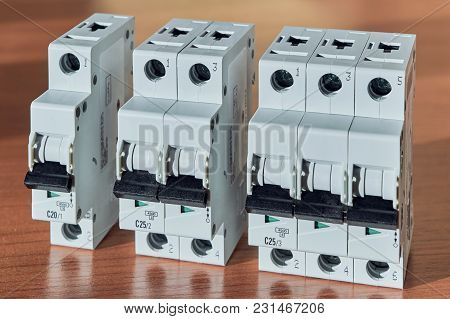 Three Modular Electrical Circuit Breakers On The Table. The Switch Is Single-pole, Double-pole And T