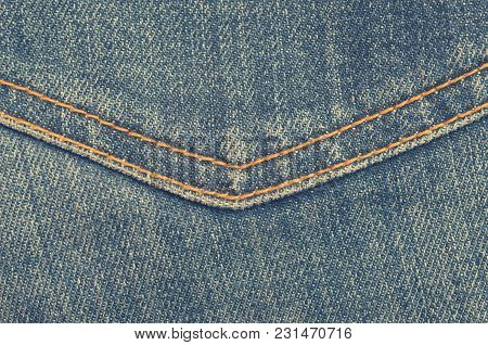 Textile Texture Of Blue Jeans With Orange Stitching