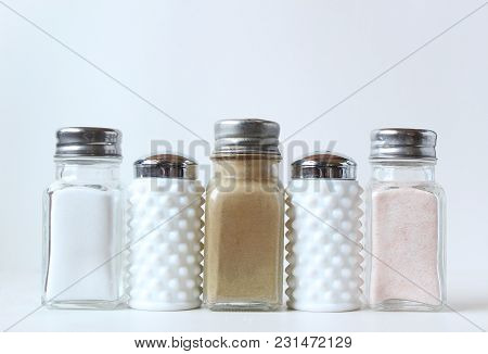 A Variety Of Salt And Pepper Shakers In A Row. White Copy Space.