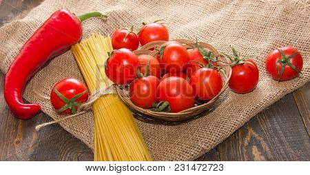 Long Vermicelli Macaroni With Ripe Cherry Tomatoes On A Wooden Table On A Beige Bag