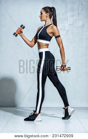 Perfect Sporty Woman Working Out With Dumbbells. Photo Of Woman In Black Sportswear On Grey Backgrou