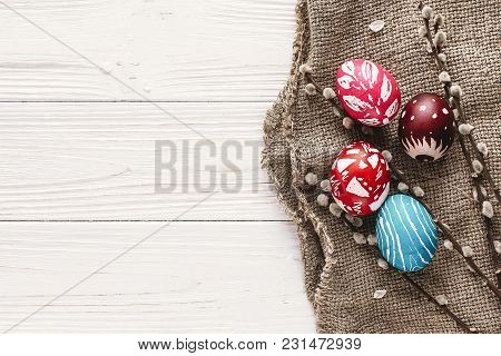 Stylish Easter Flat Lay. Painted Eggs On Rustic Wooden Background With Spring Willow Branches. Happy