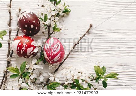 Stylish Painted Easter Eggs On Rustic Wooden Background With Spring Flowers And Willow Branches. Hap