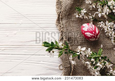 Stylish Easter Flat Lay. Painted Egg On Rustic Wooden Background With Spring Flowers And Willow Bran