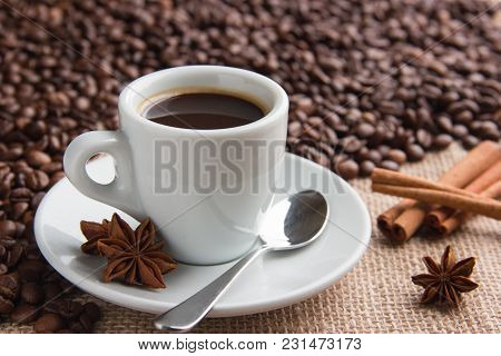A Cup Of Espresso On A Saucer With A Spoon And Aniseed Cinnamon Sprigs And Roasted Coffee Beans