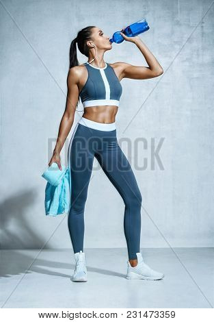 Sporty Girl Drinking Water After Workout. Photo Of Latin Fitness Girl On Grey Background. Healthy Li