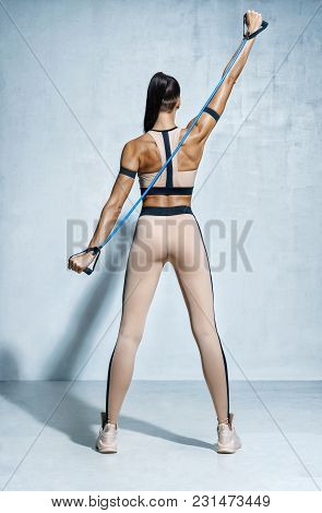 Fitness Girl Performs Exercises For The Muscles Of The Back And Hands With Resistance Band. Photo Of