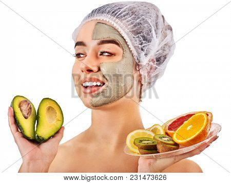 Avocado clay face mask. Woman in medical hat holding half of green fruit isolated background. Facial beautiful procedure concept. Masks for skin created from natural ingredient. Acne Removal.