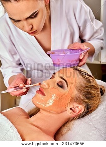 Collagen face mask. Facial skin treatment. Woman receiving cosmetic procedure in beauty salon. Bottle with moisturizing cream on background. Mask against black dots. Removal of pigmented spots.
