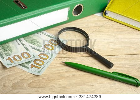 Accounting Books, Money, Magnifying Glass And Pen On Wooden Office Table. Financial And Budget Conce