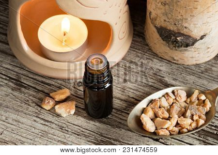 A Bottle Of Styrax Benzoin Essential Oil With Styrax Benzoin Resin And An Aroma Lamp In The Backgrou