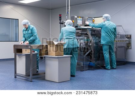 Pharmaceutical Technicians Work In Sterile Working Conditions At Pharmaceutical Factory. Scientists