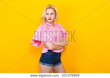 Woman With Red Lips In Pink Shirt And Jeans Shorts Pose With Crossed Arms On Orange Background With