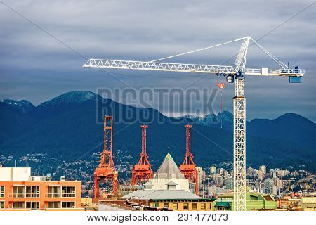 The Building Tower Crane Towers Over A Modern City With Tall Buildings And Over Mountains Covered Wi