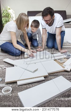 The Family Is Kneeling On A Beige Carpet. In Front Of Them Is A Furniture Assembly Manual, Which The