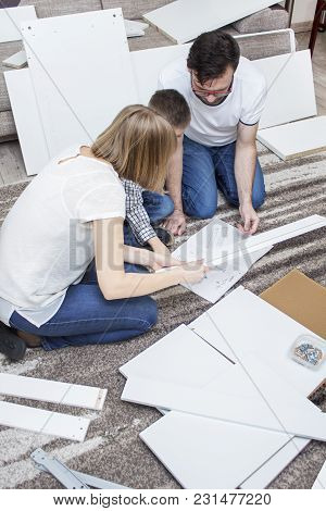 6.	Mom, Dad And Son, Kneeling Over The Instructions In The Living Room On The Carpet. Around Them La