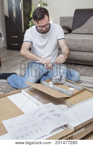 The Man Kneels On The Carpet Above The Cardboard Box With Elements Of Furniture For Self-assembly An