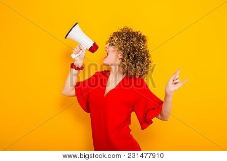 Portrait Of A White Woman With Afrro Curly Hairstyle In Red Dress And Sunglasses Shouting Into Megap