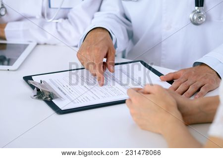 Doctor And  Patient Talking While Sitting At The Desk In Office. Physician Pointing Into Medical His