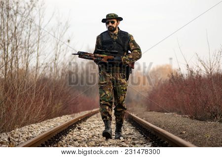 The Security Man In Military Uniform With Crossbow Weapon Is Walking On The Railway Track In Nature.